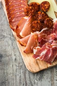 Hiszpańskie wędliny. ser, kiełbasa i szynka na drewnianym stole