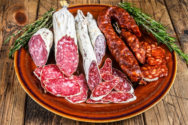 Hiszpańskie wędliny z salami, fuetem i chorizo pokrojonymi w plasterki na rustykalnym talerzu