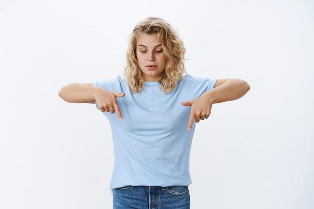 Hmm co to jest. portret ciekawskiej i zainteresowanej, ładnej klientki z blond kręconymi włosami w niebieskiej koszulce wskazuje w dół i patrzy zaintrygowaną w dół na reklamę nad białą ścianą
