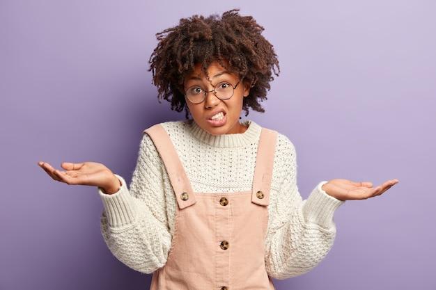 Hmm, co wybrać? nieświadoma, dobrze wyglądająca kobieta ma kręcone włosy, podnosi ręce, czuje wątpliwości, nosi biały sweter i kombinezon, odizolowana na fioletowej ścianie, zaciska zęby z niezadowolenia