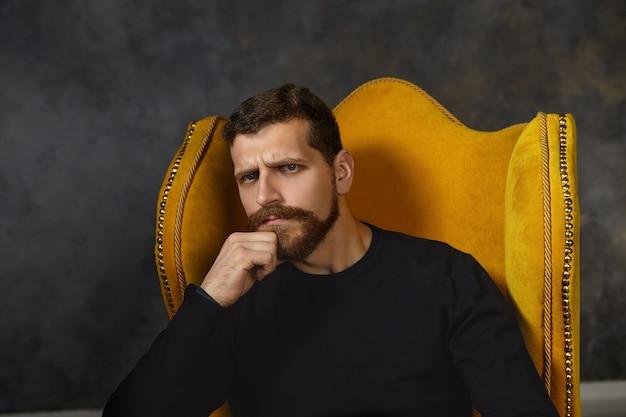Hmm. wątpliwy nieogolony mężczyzna marszczący brwi, wahający się przed podjęciem jakiejś decyzji, siedzący samotnie w fotelu w pomieszczeniu, pocierający brodę, szukający idealnego rozwiązania lub pomysłu, niepewny i sfrustrowany