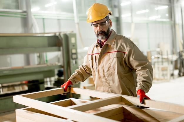 Hndsome pracownik w średnim wieku pracuje w fabryce mebli