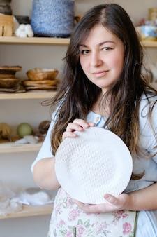 Hobby ceramiki rzemieślniczej. piękna kobieta rzemieślniczka przedstawiająca ręcznie robiony talerz gliny