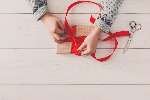 Hobby dla majsterkowiczów, kobiece dłonie zawijające świąteczne lub inny świąteczny ręcznie robiony prezent