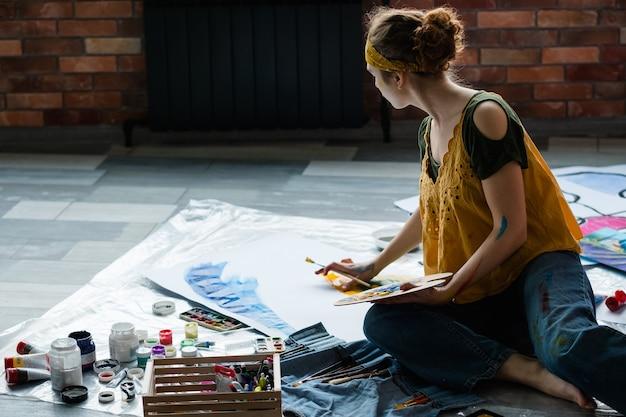 Hobby i rekreacja artystyczna. artystka siedzi na podłodze, używając palety farb akrylowych, tworząc abstrakcyjne dzieła sztuki.