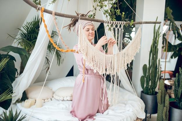 Hobby, Makrama. Młoda Dorosła Skoncentrowana Uprzejma Kobieta W Szlafroku, Tkająca Makramę Na łóżku W Pobliżu Roślin Doniczkowych Premium Zdjęcia