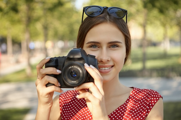 Hobby, rozrywka, zawód i koncepcja czasu letniego. urocza szczęśliwa młoda studentka robi zdjęcia ludzi i przyrody w parku przy użyciu aparatu dslr, uśmiechnięta, o radosnym wyrazie twarzy