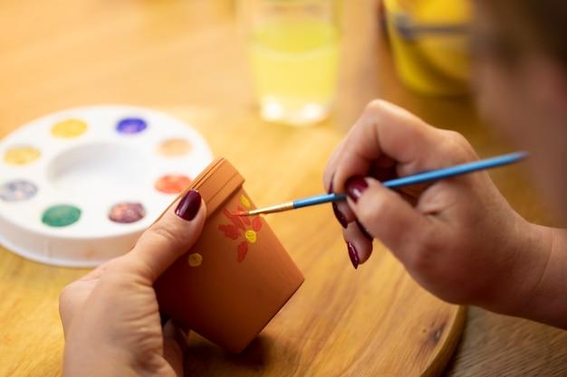 Hobby rysowania kobiecych rąk, malowanie doniczki farbami