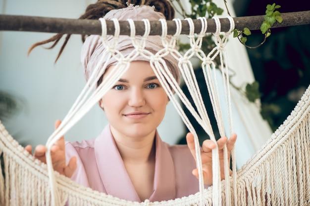 Hobby. śliczna młoda kobieta waeving i patrząc pozytywnie