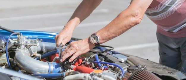 Hobby starszego mężczyzny naprawiającego silnik samochodu na zewnątrz