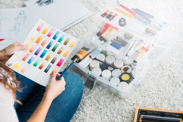 Hobby sztuki. artystka siedząca zrelaksowana na podłodze z próbką koloru farby i ołówkami