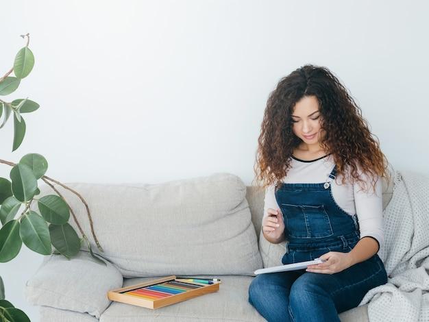 Hobby sztuki domowej. kobieta siedzi na podłodze z kredkami i zestaw do malowania, uśmiechając się.