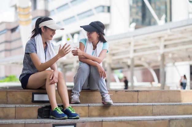 Hojna dziewczyna daje butelkę wody przyjacielowi przed godz