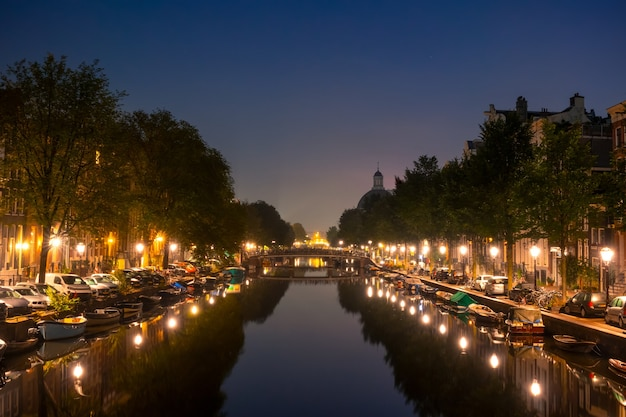 Holandia. noc w amsterdamie. przy brzegach kanału cumuje wiele łodzi. latarnie i samochody zaparkowane na nasypach