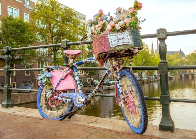 Holandia. pochmurny poranek nad kanałem w amsterdamie. przy płocie mostu zaparkowany jest ozdobiony kwiatami rower ze znakiem love