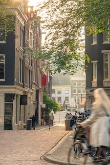 Holandia. słoneczny poranek na ulicy amsterdamu. dziewczyna na rowerze z rozmyciem ruchu i mnóstwem rowerów