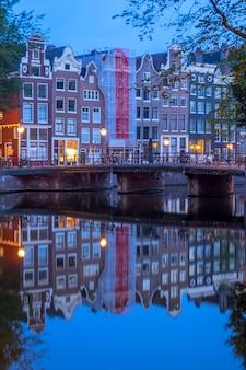 Holandia. wczesny poranek w amsterdamie. most z zaparkowanymi rowerami i odbiciami tradycyjnych domów w wodzie kanału