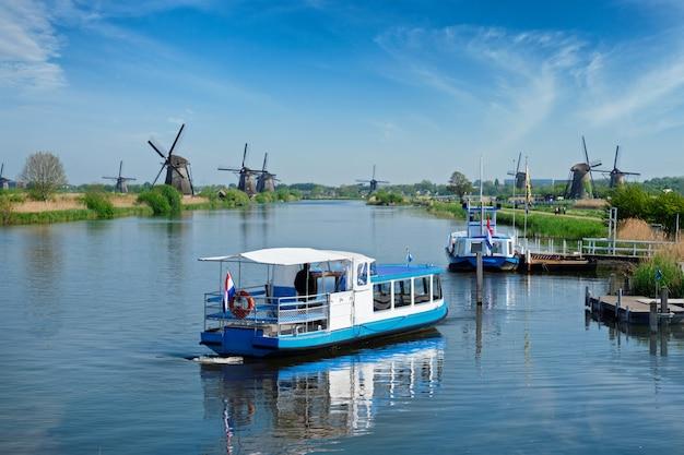 Holandia wiejski lanscape z turystyczną łodzią i wiatraczkami przy sławnym miejscem turystycznym kinderdijk w holandia