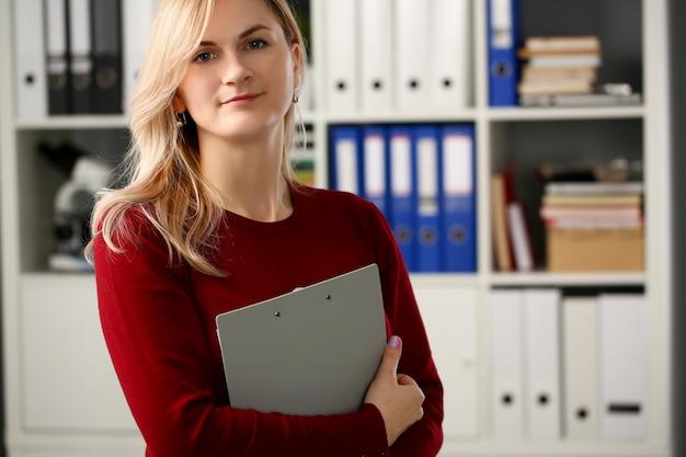 Holdig szczęśliwy uśmiechnięty blond bizneswoman