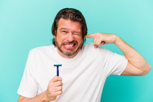 Holender średnim wieku trzyma żyletkę na białym tle na niebieskiej ścianie obejmujące uszy rękami