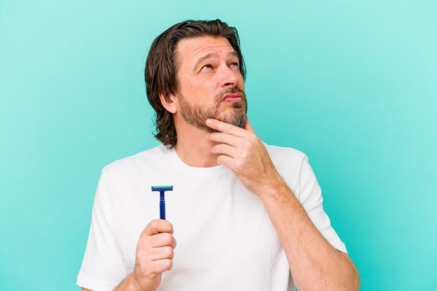 Holender średniowiecza trzymający żyletkę na białym tle na niebieskiej ścianie, patrząc w bok z wątpliwym i sceptycznym wyrazem twarzy.