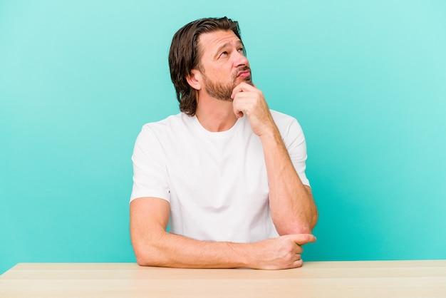 Holender w średnim wieku, siedzący na białym tle na niebieskiej ścianie, patrząc w bok z wyrazem wątpliwości i sceptycyzmu
