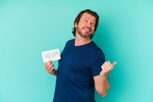 Holender w średnim wieku, trzymając plakietkę pomocy na białym tle na niebieskiej ścianie, z dala od kciuka, śmiejąc się i beztrosko