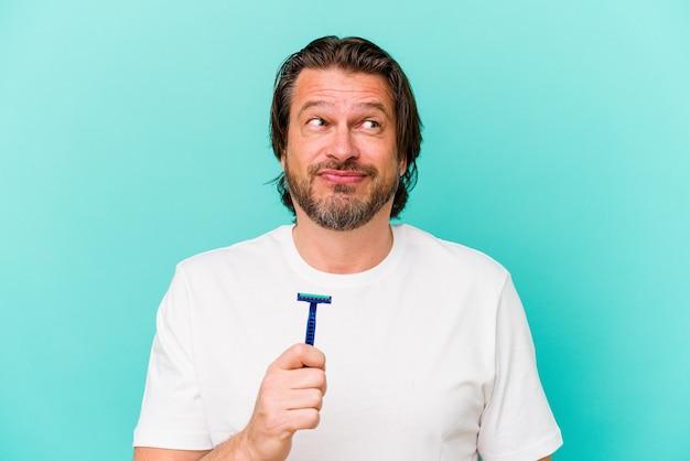 Holender w średnim wieku, trzymający żyletkę na białym tle na niebieskim tle, jest zdezorientowany, czuje się niepewny i niepewny.