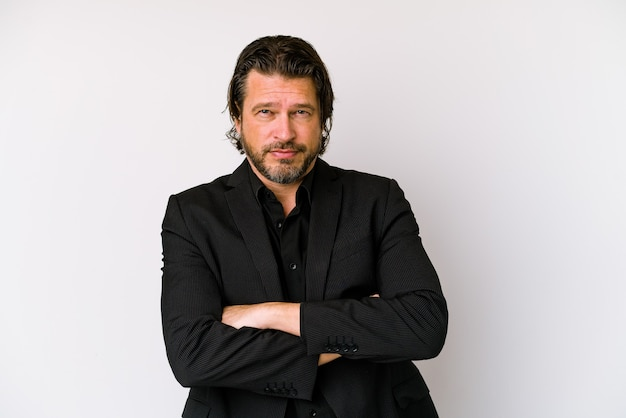 Holenderski mężczyzna w średnim wieku na białej ścianie uśmiechnięty pewnie ze skrzyżowanymi rękami.
