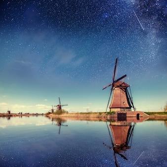 Holenderski młyn nocą. gwiaździste niebo. holandia holandia.