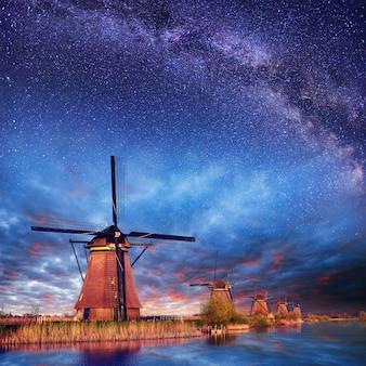 Holenderski młyn nocą. gwiaździste niebo. holandia.