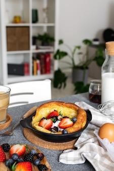 Holenderski naleśnik ze świeżymi jagodami, filiżanka cappuccino