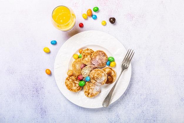 Holenderskie mini naleśniki zwane poffertjes z kolorowym cukrem pudrem i cukierkami. koncepcja zdrowej żywności, leżał na płasko, widok z góry, miejsce