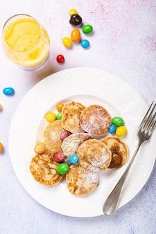 Holenderskie mini naleśniki zwane poffertjes z kolorowym cukrem pudrem i cukierkami. koncepcja zdrowej żywności, płaski świeckich, widok z góry