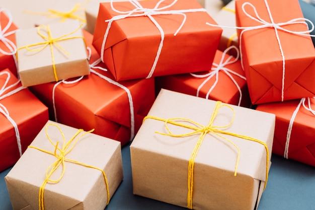 Holiday przedstawia pakowanie i dostawę. mieszanka prezentów zawiniętych w czerwony i rzemieślniczy papier i przewiązanych sznurkiem. koncepcja uroczystości i gratulacji.