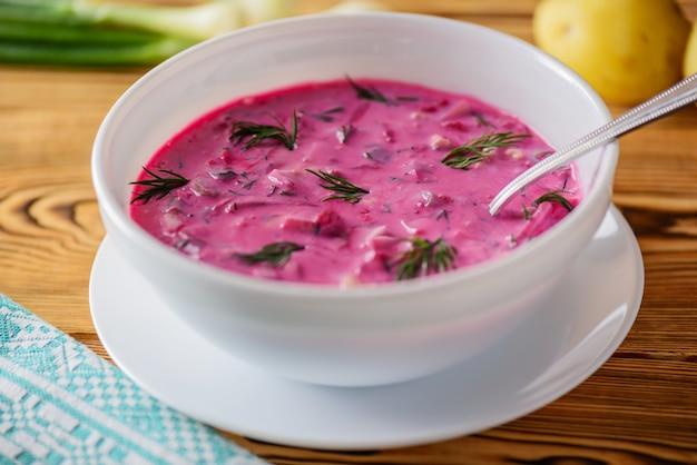 Holodnik buraków, jaj i zieleni na drewnianym stole. rosyjska tradycyjna kuchnia.