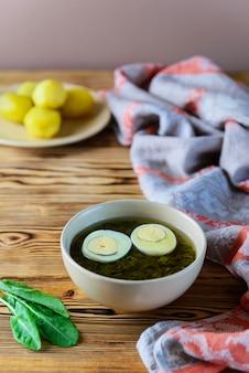 Holodnik szczawiu, jajka i zieleni na drewnianym stole.