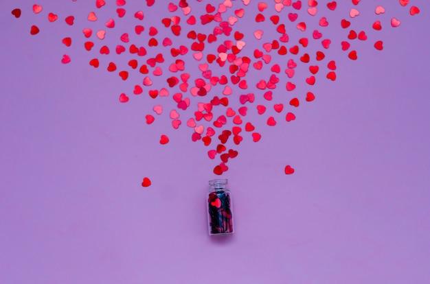 Holograficzne serca na modnym fioletowym tle. świąteczne tło. widok z góry.