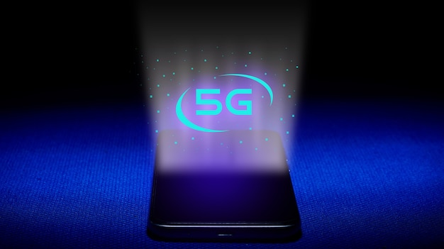 Hologram 5g. smartfon i obraz hologramu 5g na niebieskim tle. koncepcja technologii 5g to nowa generacja sieci. - wizerunek