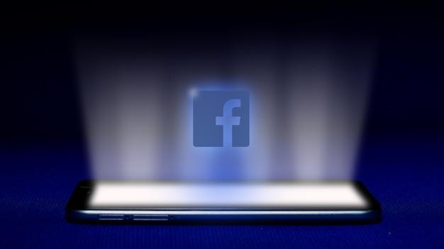 Hologram z logo facebooka. hologram facebook logo obraz na niebieskim tle.