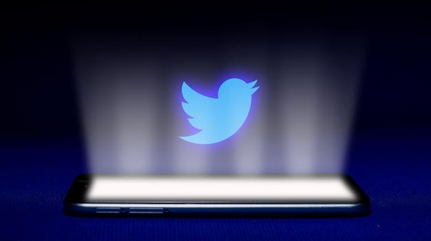 Hologram z logo twittera. hologram twitter logo obraz na niebieskim tle.