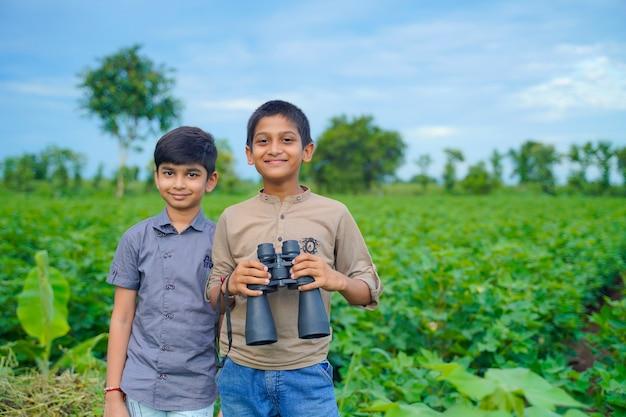 Holowniczy mały indyjski chłopiec bawi się na łonie natury z lornetką
