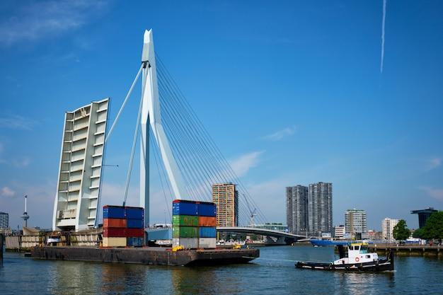 Holownik holujący barkę z kontenerami pod otwartą zwodzoną częścią mostu erasmusbrug na rzece nieuwe maas.