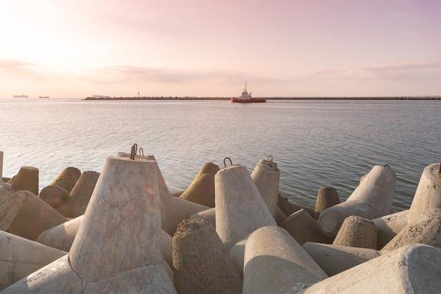 Holownik pływa na pełnym morzu, aby holować statek towarowy do portu. piękny zachód słońca nad molo. falochrony czworonogów w porcie.