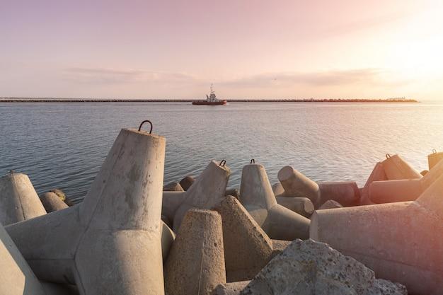 Holownik pływa na pełnym morzu, aby holować statek towarowy do portu.