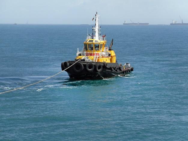Holownik w oceanie wciąga statek do portu