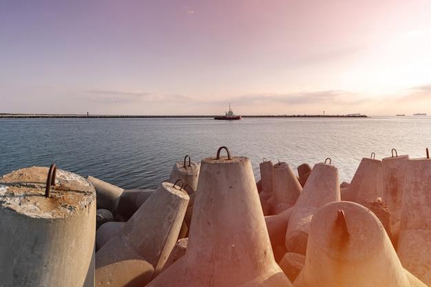 Holownik żegluje w morzu holować statek do portu. falochrony czworonogów w porcie. piękny zachód słońca nad molo.