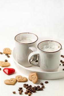 Holuj filiżankę cappuccino z ciasteczkami jak serca