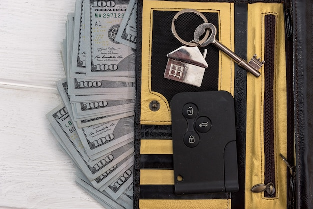 Homa nad kluczyki do samochodu z banknotów dolarowych na stole. koncepcja oszczędzania