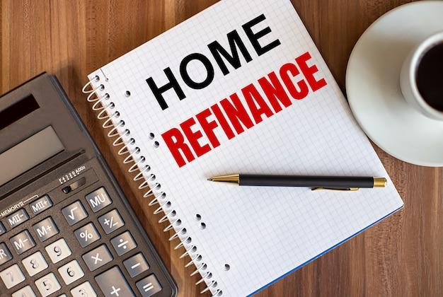 Home refinance napisane w białym notatniku obok kalkulatora i filiżanki kawy na ciemnej drewnianej powierzchni